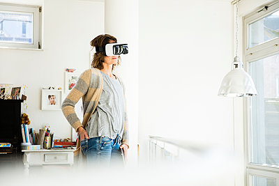 Woman wearing VR glasses at home - p300m1568299 by Robijn Page
