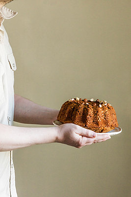 Mid section of man holding plate with zucchini cake - p300m2198157 by Eva Gruendemann