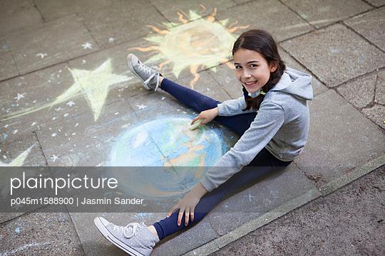 Mädchen malt mit Straßenkreide - p045m1588900 von Jasmin Sander