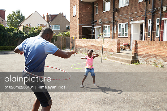 Father and daughter playing with plastic hoops in sunny neighborhood - p1023m2238491 by Himalayan Pics