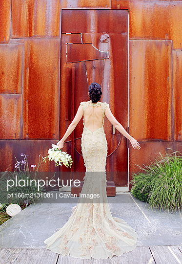 Back view of Bride with Bouquet in custom Lace wedding gown - p1166m2131081 by Cavan Images