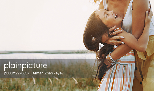 Mother embracing daughter by lake - p300m2273697 by Arman Zhenikeyev