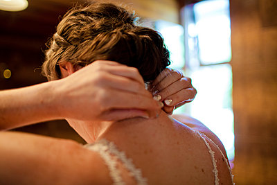Rear view of bride wearing necklace while standing at home - p1166m2067543 by Cavan Images