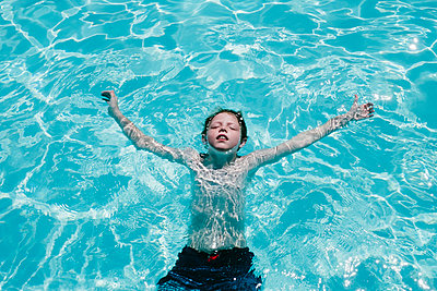 Child floating in pool on his back - p1262m1444773 by Maryanne Gobble