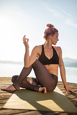 Woman sitting on jetty at a lake practicing yoga - p300m1549717 by Daniel Waschnig Photography