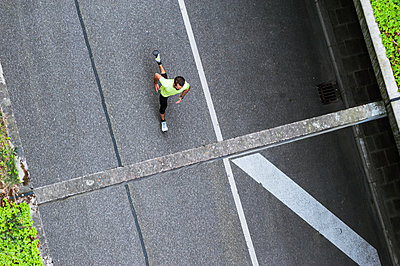 Top view of man running on a street - p300m1587142 by Daniel Ingold