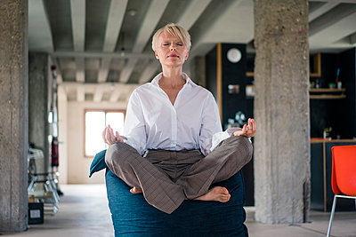 Blond businesswoman meditating while sitting on beanbag at home - p300m2266968 by Robijn Page