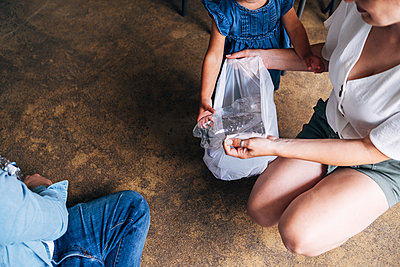 Woman collecting crushed plastic bottle for recycling while crouching by family on floor - p300m2293277 by Angel Santana Garcia