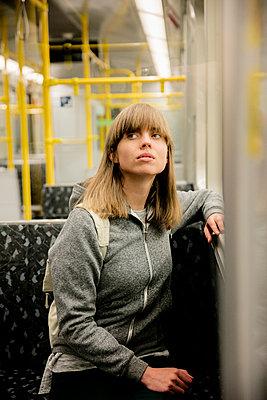 Junge Frau mit Rucksack sitzt in der U-Bahn - schaut nach oben - p1212m1137016 von harry + lidy