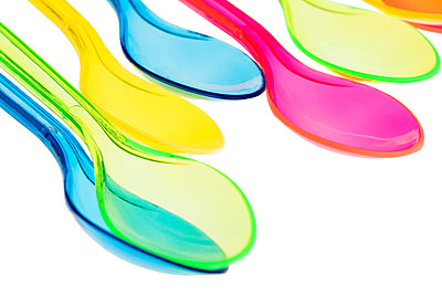 Coloured transparent plastic disposable spoons on white background - p1302m2045581 by Richard Nixon