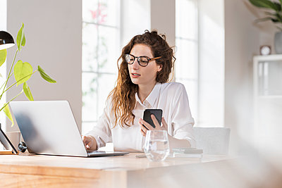 Female professional with eyeglasses working on laptop while holding smart phone at desk - p300m2277527 by Steve Brookland