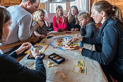 Family playing board game - p312m2079837 by Fredrik Schlyter