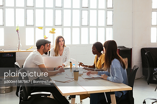 Colleagues working together at desk in office - p300m1587567 von Bonninstudio