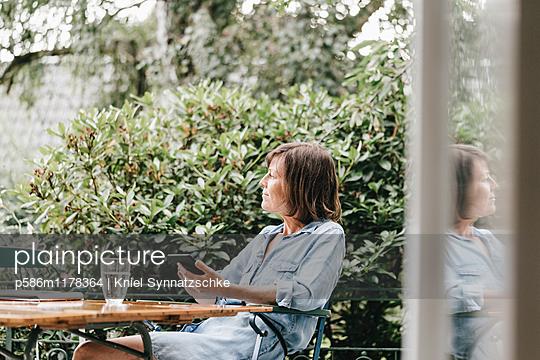 Woman with e-book on terrace - p586m1178364 by Kniel Synnatzschke
