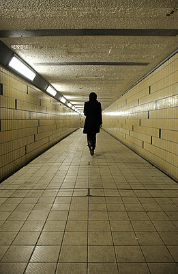 Figure walking away down an underground tunnel - p1072m829392 by Neville Mountford-Hoare
