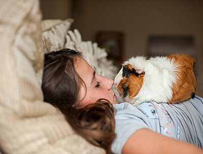 Side view of girl with guinea pig lying on bed at home - p1166m2067869 by Cavan Images