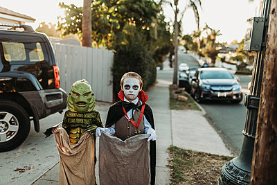 Young siblings dressed in Halloween costumes during Trick-or-Treat - p1166m2208371 by Cavan Images