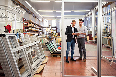 Two businessmen in factory looking at tablet - p300m1562400 by Daniel Ingold