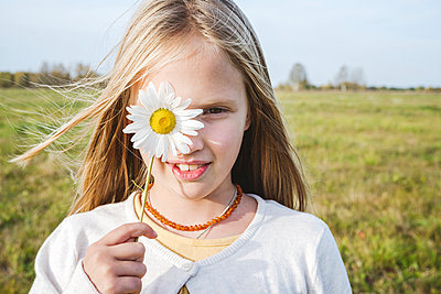 Cute girl covering eye with chamomile flower at field - p300m2225494 by Ekaterina Yakunina