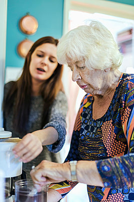 Grandmother and granddaughter preparing coffee at home - p426m1151723 by Maskot
