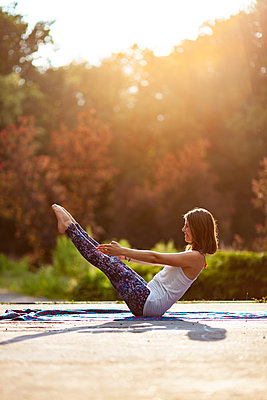 Young woman practicing yoga in park - p795m2199806 by JanJasperKlein