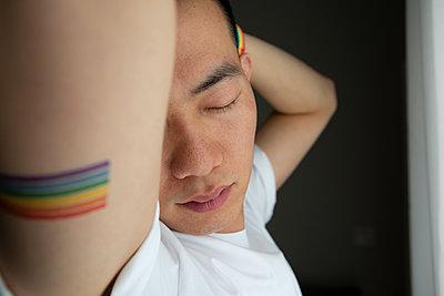 Asiatischer Mann mit Regenbogenfahne, Portrait - p817m2270144 von Daniel K Schweitzer
