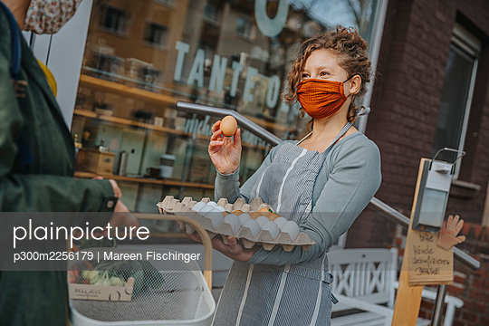 Female clerk in mask selling eggs to customer at organic retail store during COVID-19 - p300m2256179 by Mareen Fischinger