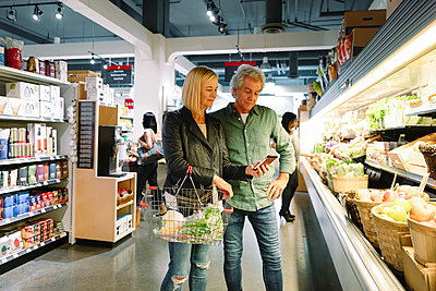 Senior couple with smart phone shopping for produce in grocery store - p1192m2110015 by Hero Images