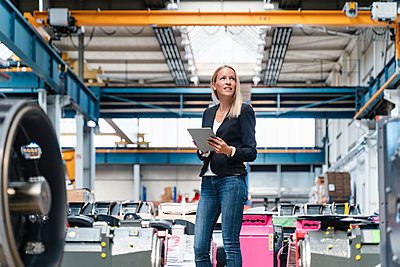 Businesswoman holding digital tablet looking away while standing in factory - p300m2240099 by Daniel Ingold
