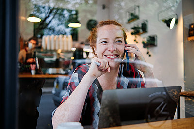 Smiling woman looking away while talking on smart phone at cafe - p300m2287287 by Angel Santana Garcia