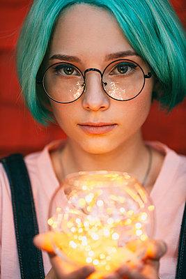Teenage girl wearing eyeglasses holding illuminated string lights - p301m1498613 by Vasily Pindyurin