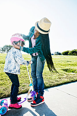 Black mother fastening helmet on daughter - p555m1306113 by Peathegee Inc