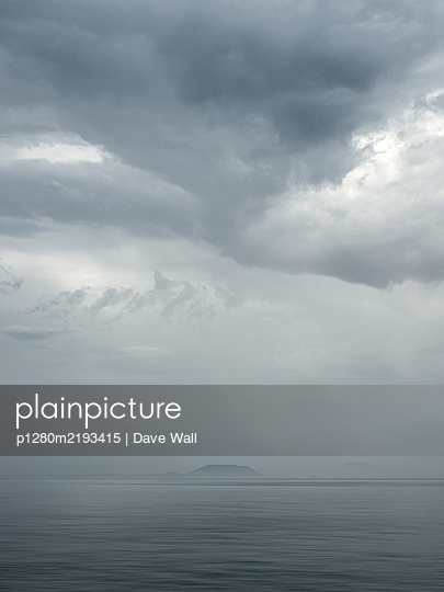 Storm clouds over the sea and mountain range in the fog - p1280m2193415 by Dave Wall