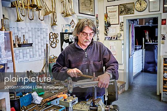 Instrument maker repairing trumpet in workshop - p300m1156964 by Dirk Kittelberger