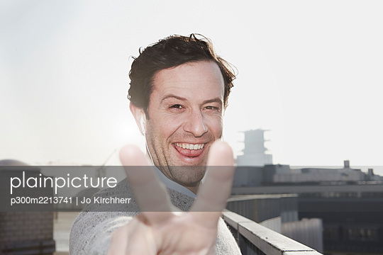 Portrait of smiling man showing victory sign - p300m2213741 by Jo Kirchherr