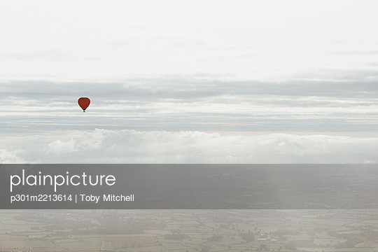 Red hot air balloon in sunny cloudy sky above Bath, Somerset, UK - p301m2213614 by Toby Mitchell