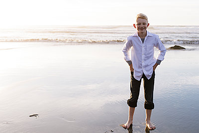 Portrait of smiling boy standing on the water at the beach - p1166m2073864 by Cavan Images