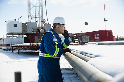 Male worker talking cell phone snowy gas plant - p1192m1128013f by Hero Images