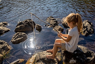 Girl fishing on the lakefront - p1355m1574070 by Tomasrodriguez