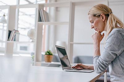 Woman using laptop at desk in office - p300m1549643 by Kniel Synnatzschke