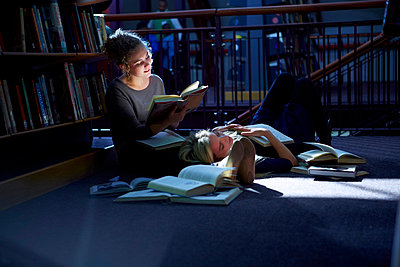 Female student lying on floor in a library with friend reaing book - p300m975525f by zerocreatives