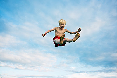 Boy jumping mid-air - p312m1113740f by Johan Willner