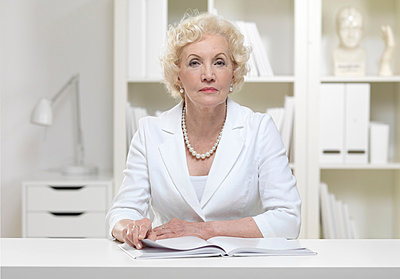 Serious senior businesswoman with book - p429m819544 by Colin Hawkins