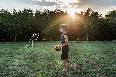 Boy playing football in park - p924m1495087 by Bonfanti Diego