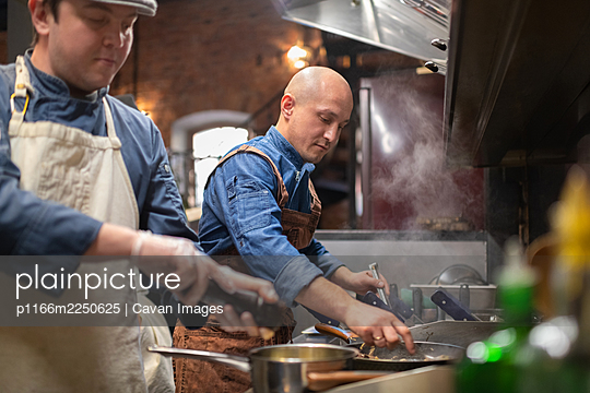 Male chef frying dish near colleague - p1166m2250625 by Cavan Images