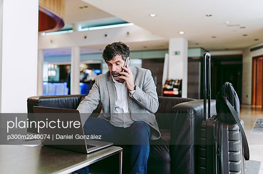 Businessman talking on phone while using laptop in hotel lobby - p300m2240074 by Daniel González