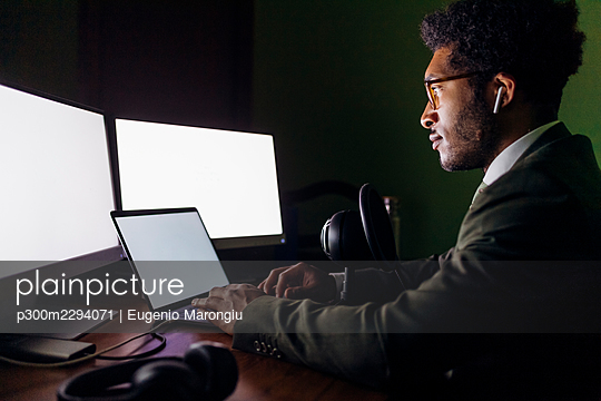 Businessman with microphone using laptop while working at home office - p300m2294071 by Eugenio Marongiu