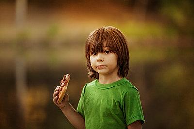 Portrait of boy holding pizza slice - p1166m1098868f by Cavan Images
