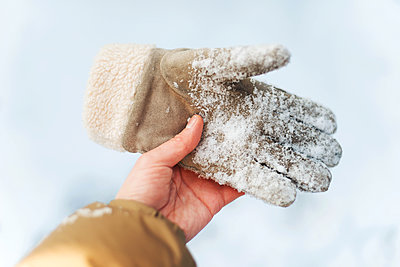 young woman  holding glovee in snow   in her hands - p1166m2255371 by Cavan Images