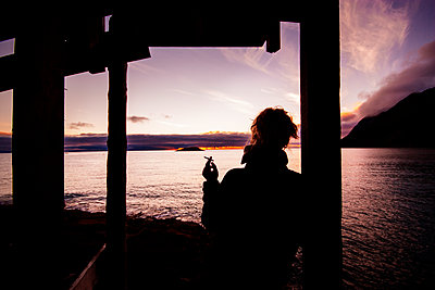 Rear view of silhouette woman smoking while leaning on pole during sunset - p1264m1121835f by Rebecca Gustafsson